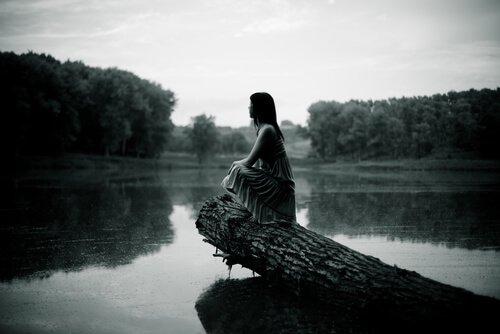 mujer-triste-sola-sentada-en-el-tronco-de-un-arbol
